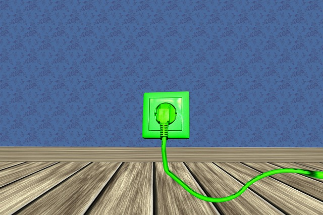 zelená zásuvka a zástrčka, modrá stěna